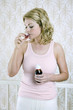 A woman drinking cough syrup