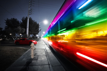 Rainbow spectrum blurred motion city bus at night