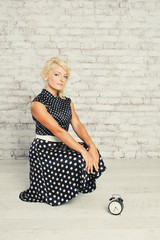 Young blonde girl in dress sitting with clock in studio