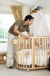 Man playing with baby in a crib