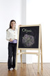 Girl smiling and holding onto blackboard