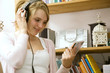 Girl looking at CD while listening to music on the headphones