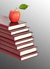 Red apple on pile of books on  background