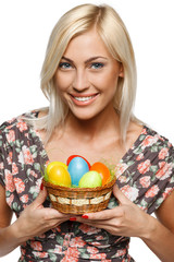 Closeup of happy female holding basket with Easter eggs