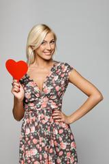 Female in summer dress holding red heart shape