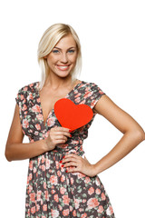 Female holding red heart shape near her heart