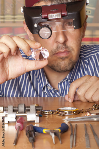 jeweler looking in a diamond.  Focus on diamond
