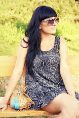 Portrait of a beautiful young woman in sunglasses posing outdoor