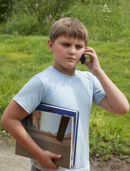 The serious boy of 10 years speaks with books by phone against a