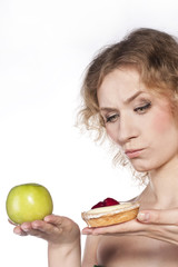 Young cheerful woman, choosing between apple and cake