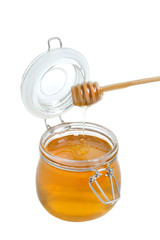 Open jar of honey and drizzler on a white background