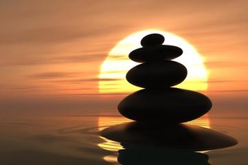 Zen pebbles stacked in sunset