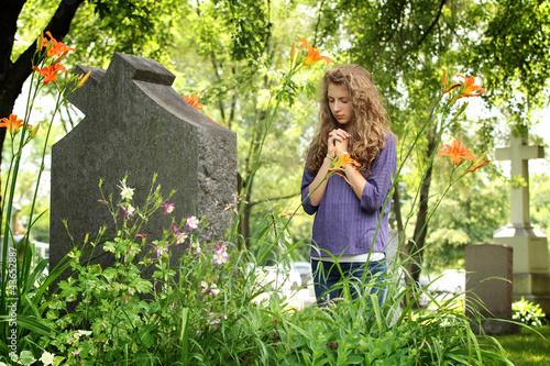 Girl praying at the cemetery