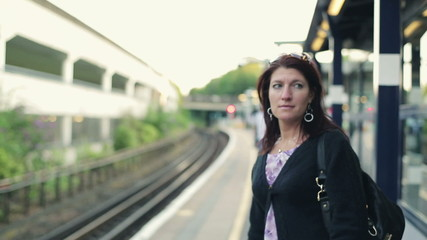 Woman waiting for a train on station, steadicam shot