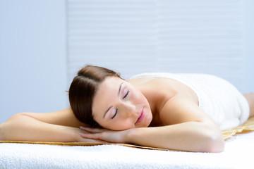 junge frau liegt entspannt auf einer massageliege