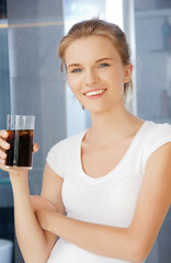 happy and smiling teenage girl with glass of cola