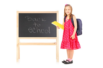 Schoolgirl holding a notebook and posing next to a board