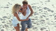 Energetic attractive couple dancing at the beach