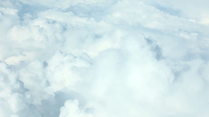 Airplane flying above puffy clouds
