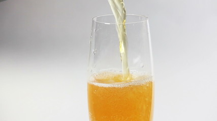 Cider flowing into the glass with bubbles isolated on white