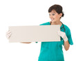 young smiling nurse or doctor showing empty board