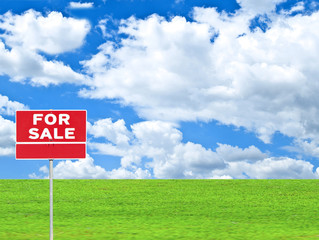 """LAND FOR SALE SIGN"" on empty meadow - Real estate conceptual im"