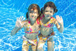 Happy smiling underwater children in swimming pool on vacation