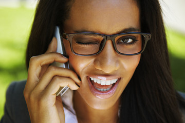 beautiful african businesswoman winking - talking phone