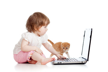 kid girl playing with kitten and laptop