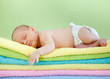 newborn baby girl sleeping on colourful towels