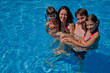 Happy family with two kids in swimming pool. Summer vacation