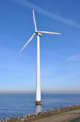 Modern windmill in the water near the shore