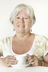 Smiling senior lady sitting at table holding a cup of tea