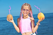 Little girl with fruit on the beach