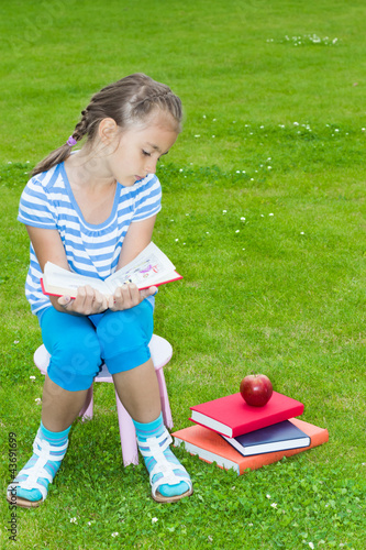 The small girl sitting on a chair looks at an apple