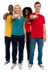 Cheerful group of teenagers pointing at you