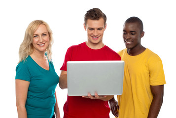 Cheerful group of friends working on laptop