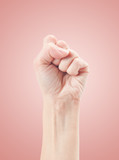 Fist. Gesture of the hand on pink background.