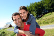 Man giving piggyback ride to girlfriend on a trekking day