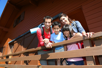 Portrait of family standing on log cabin front door