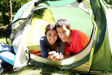 Portrait of cheerful couple relaxing in camp tent
