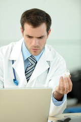 Closeup of doctor holding pills in front of laptop