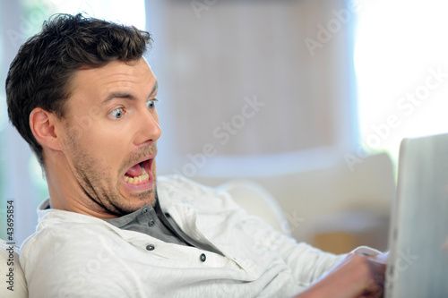 Man in sofa with scared look in front of tablet