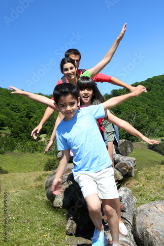 Family of four standing on rocks in the mountain