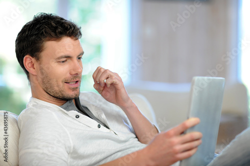 Man in sofa using electronic tablet