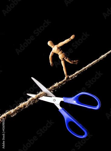 Tijera cortando la cuerda de un equilibrista.
