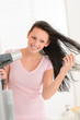 Smiling woman blow-drying long hair