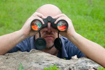 Bald man watching the nature through binoculars