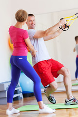 Man exercising with personal trainer