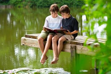 Zwei jungendliche Freunde lesen ein Buch am Teich